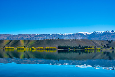 Beautiful snow capped Southern Alps reflections on Lake Dunstan in New Zealand