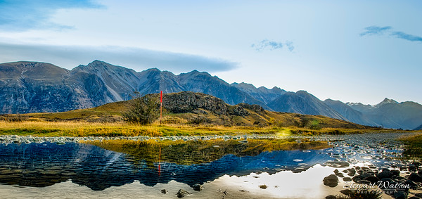 Mount Sunday (Edoras) reflected in a rain puddle dwarfed by the massive Southern Alps