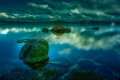 Moss and slime covered rocks in Lake Tarawera New Zealand as night approaches