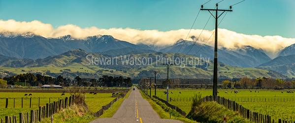Rural road from the Eastern hills to the cloud covered Tararua ranges in Wairarapa New Zealand