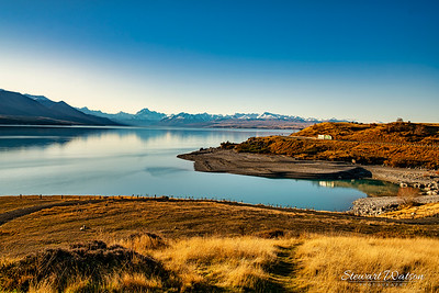 The bays and shore of a very calm Lake Pukaki with the snow covered peaks of the Southern Alps in the distance looking back towards Twizel