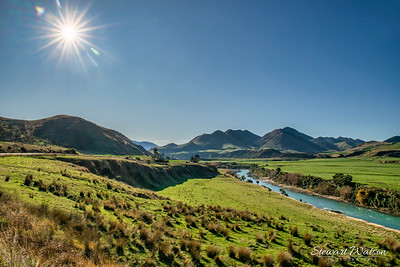 Sun Flare over the Maruia River flowing through farmland in  the Lewis Pass