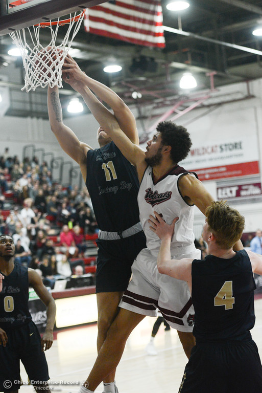. Chico State\'s Matt Kimura (5) goes up for a shot against Monterey Bay\'s Anthony Booker (11) and Koen Sapwell (4), Thursday, February 1, 2018, in Chico, California. (Carin Dorghalli -- Enterprise-Record)