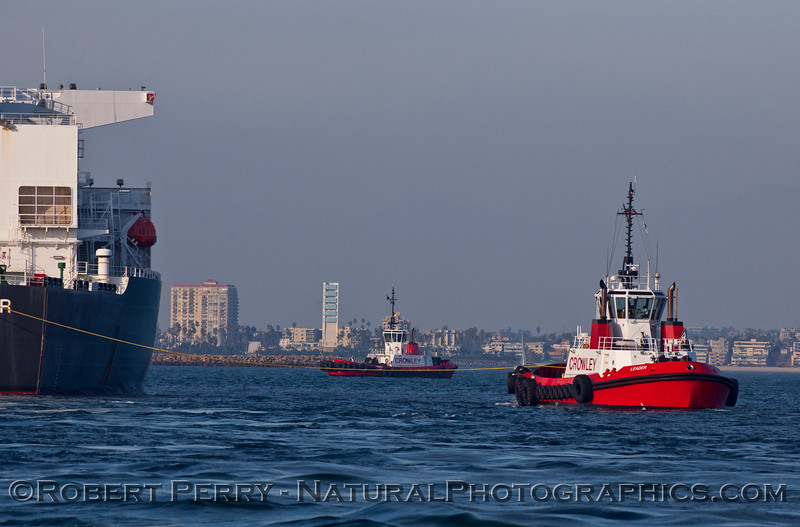 "Two Crowley towboats, ""Leader"" with a stern line, and ""Admiral"" in the back, help guide the oil tanker ""Alaskan Navigator"" into Long Beach Harbor."