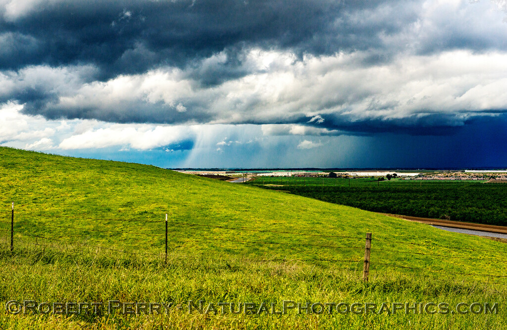 Sunny foreground contrasted with the dark clouds and heavy rains in the distance.