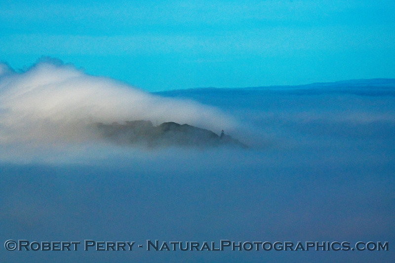 Point Sur and its lighthouse seen in the distance surrounded by an ocean fog and waves of dense fog
