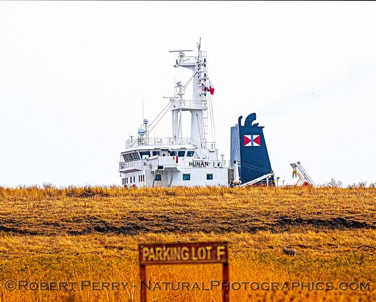 Bulk carrier vessel Hunan - main bridge seen moving along above the berm.