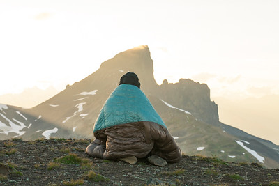 A young woman stays warm on her sleeping bag while watching the sun set over Black Tusk Mountain in Garibaldi Provincial Park, British Columbia, Canada.