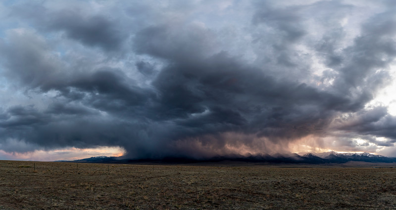 A massive anvil cloud envelops the Sangre de Cristo Mountains.