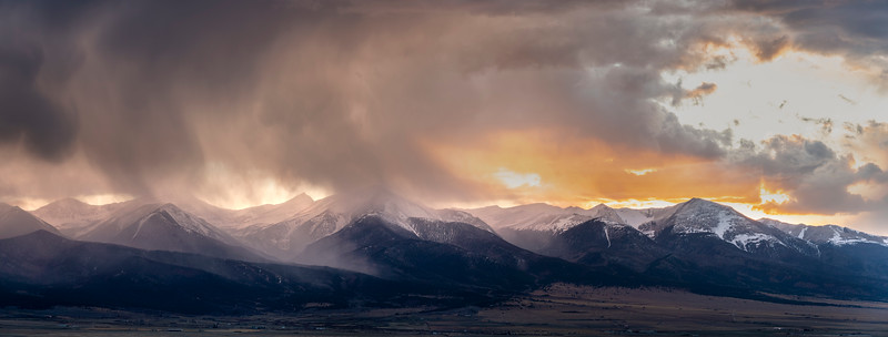 The setting sun shines through the storm over the Sangre de Cristo Mountains.   Silver Cliff, CO