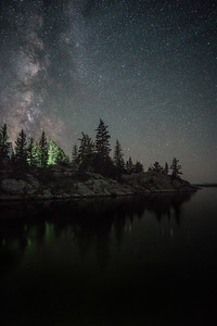 The glow of a campfire lights up the trees under the Milky Way.  Eleven Mile Reservoir.