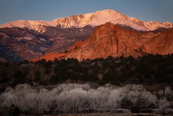 Morning alpenglow lights up Pikes Peak and Garden of the Gods over Colorado Springs.