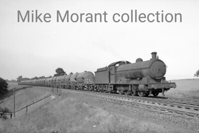 LOCATION?????? LNER Raven Q6 class 0-8-0 no. 3392 depicted with a rake of chemical or oil tank wagons and taken before BR branding was applied in May 1948. 3392 was a West Hartlepool engine at nationalisation and would remain so until withdrawal in November 1963. [Mike Morant collection]
