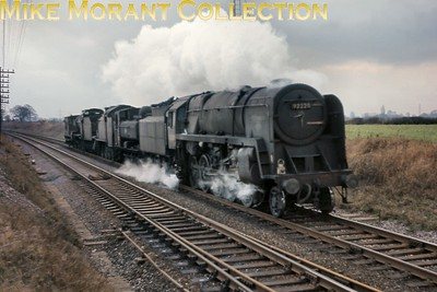 An interesting and unusual image featuring careworn BR Standard 9F 2-10-0 no. 92220, shorn of nameplates, hauling three 'dead' locomotives which are an as yet unidentified Collett 5700 class pannier tank (probably 4610 or 9729), Maunsell 'Z' class 0-8-0T no. 30952 and Fowler S&D 7F 2-8-0 no. 53807 en route from Bristol (Barrow Road) mpd to Severn Tunnel Jct. mpd. Both 30952 and 53807 are recorded as being present at STJ on 7/3/65.  The location is Hall End level crossing between Yate and Wickwar. [Mike Morant collection]