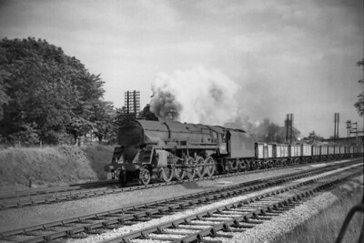 Wellingborough allocated BR Standard Franco-Crosti boilered 9F 2-10-0 no  92027 in charge of a rake of empty mineral wagons on the Down Slow line at Great Bowden just north of Market Harborough on 31/7/56. [Mike Morant collection]
