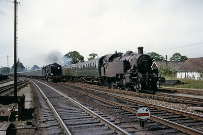 Bulleid rebuilt Merchant Navy pacific no. 35005 Canadian Pacific, in charge of the 09.23 Bournemouth - Waterloo train,.passes the Lymington branch train hauled by Bournemouth allocated Ivatt 'Mickey Mouse' 2MT 2-6-2T no. 41295 at Brockenhurst on June 7th, 1965. 41295 didn't quite see out the end of SR steam being withdrawn at 71A in April 1967. 35005 survived into the heritage era and was well known in the 1990's for its forays in blue livery on main line excursions. [Mike Morant collection]