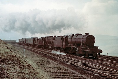 A pair of careworn Stanier 8F 2-8-0's with no. 48268 as pilot are in charge of a northbound tracklaying train as it approaches Dent station on the Settle & Carlisle line. A viewer has informed me that this was a regular Sunday working with a payload of about 1,000 tons and was known as The Blackburn Rails. [Mike Morant collection]