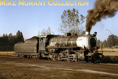 """At Greenside Colliery (Blackhill, Witbank district, Transvaal), an ex-South African Railways S-class 0-8-0 locomotive prepares to collect a train of coal wagons from the loading area destined for the SAR exchange sidings in 1980. Two S-class locomotives (SAR nos. 367 and 362) would eventually carry Greenside numbers 5 & 6 but this one was unnumbered when photographed, so its identity is uncertain. After major overhaul, this type would normally be supplied from Dunns Engineering (of Witbank), which also hired out such locomotives under short-term contracts. [A.E. """"Dusty"""" Durrant / Mike Morant collection]"""