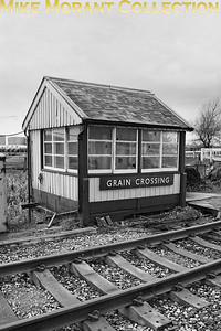 The isolated Grain Crossing signal cabin on the Hundred of Hoo line. The signalbox.org web page tells us that this quaint structure is the sole surviving Stevens & Sons signal box and is a Grade II listed building which, even more surprisingly, is till active. This shot isn't dated but it's worth noting that the cabin looks to be in a good state and the nameboard is typically BR(S) although I think that this could have been taken as late as the early 1990's. [Mike Morant collection]