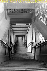 An undated view of a staircase from platform to street level at East Brixton station on the SLL (South London Line) netgween Victoria and London bridge via Peckham Rye. Opened as Loughborough Park station by the LBSCR on 13/8/1866, East Brixton was renamed Loughborough Park and Brixton on 1/1/1870 but was renamed again to East Brixton on 1/1/1894. The station was closed by BRB on 5/1/7976. [Mike Morant collection]