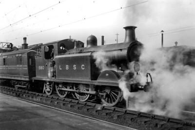 LBSCR, Billinton E5 class 0-6-2T no. 590 on passenger duty at Clapham Junction station on 5/3/1921. Unfortunately, the head signals are obscured by steam but of note is the LBSCR's overhead wires for the electric train services. [H. C. Casserley / Mike Morant collection]