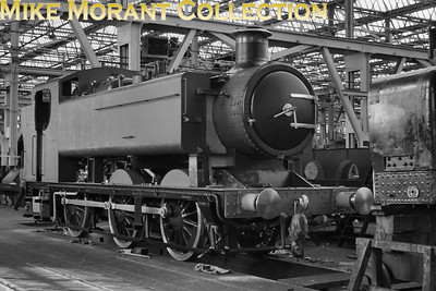 This undocumented negative was a mystery to me until a viewer suggested that this is the Hawksworth 9400 class 0-6-0PT prototype undergoing preparation in Swindon Works prior to becoming an exhibit in the Swindon Steam Museum. No. 9400 was one of only ten examples of this class that were built at Swindon between February and May 1947. 9400 itself was allocated to 82C Swindon from new and remained there until December 1955 but then moved to 81A Old Oak Common remaining there until withdrawal in December 1959. This refurbishment took place during 1962. [Mike Morant collection]