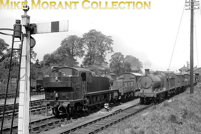 An interesting combination of motive power from different sources together in one image taken on GW & GC metals at Princes Risborough in 1938. On the left is GWR Collett prairie tank, known as a tanner oner to spotters of the fifties, no. 6138 departing southwards towards High Wycombe with a goods train whilst former GCR Robinson designed J11 'Pompom' 0-6-0 no 6047 of 1902 vintage waits with wagons attached in the siding. Note the Charringtons private owner wagon adjacent to the prairie tank. [J. H. Venn / Mike Morant collection]