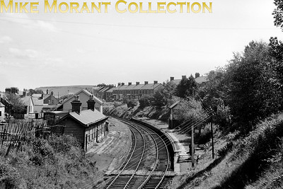 """A panoramic view across Maesteg Neath Road station taken in 1956. Although the signal box looks in good shape it isn't surprising that the station and platforms are decrepit as it had closed some 23 years before this shot was taken. [Mike Morant collection]"""