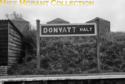 The former GWR running-in board at Donyatt Halt on the Taunton to Chard branch is depicted here on 4/4/62. Donyatt Halt was a latecomer to the GWR's network opening on 5/5/1928 some 62 years after the other stopping places on the branch and it closed along with the rest on 10/9/1962. However this scene is little changed to this day as the platform, board and passenger shelter still stand alongside a cycle path built along hte branch's trackbed. [C. L. Caddy / Mike Morant collection]