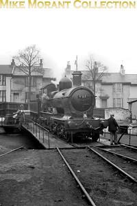 Former GWR 'Dukedog' double-framed 4-4-0 no. 9017 occupies the turntable at the unlikely location of Brighton shed on the Southern Region on 15/2/1962. 9017 had been withdrawn from BR service at (89C) Aberystwyth mpd in October 1960 and was then moved to and stored at Oswestry until its move to the heritage Bluebell Railway in January 1962. GWR locos were banned from running on former LBSCR metals and special dispensation was given for this unique journey. [Mike Morant collection]