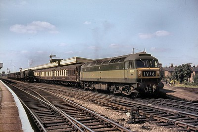 BR, Brush Type 4 Co-Co diesel no. D1740 in charge of an Up Birmingham Pullman service at Leamington Spa station. D1740, wearing the two-tone green livery that suited the class so well, was new into service at Old Oak Common depot on 12/6/64 and so was brand new when this shot was taken on an unspecified date in 1964. This service was normally operated by the famed Blue Pullmans but would be operated with a locomotive and a dedicated umber & cream set if the blue unit was unavailable for whatever reason. The steam hauled goods train on the through road is in the charge of an unidentified Stanier 'Jubilee' class 4-6-0 which still has its nameplates in situ. [Mike Morant collection]