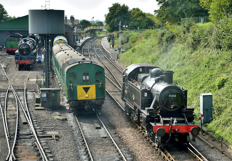 LMS/BR Ivatt Class 2MT 2-6-2 Tank No.41312 drifts through Ropley, bringing a distinctly early 60's feel to the scene as it passes  BR Standard 76017 and  DEMU No 1125  in the yard<br /> <br /> Mid Hants Railway<br /> Ropley<br /> <br /> 13 September 2016
