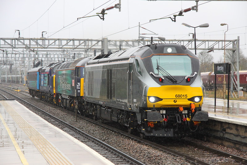 16 April 2016. The middle of April and a day which produces rain, sleet, snow and sun sees 68015 + 57307 LADY PENELOPE + 37405 + Mark 2F 5919 pass through Bletchley with snow falling working the 5A68 0723 Crewe Coal Siding - Willesden.