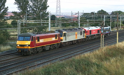 10 August 2018. Unfortunately having lost the sun only minutes earlier but still shining on the hills in the background, a record at least of 90028 + 92019 Wagner + 59202 Alan Meddows Taylor MD Mendip Rail Limited + 90024 pass Ledburn with the 0K06 1946 Wembley - Crewe Electric Depot.