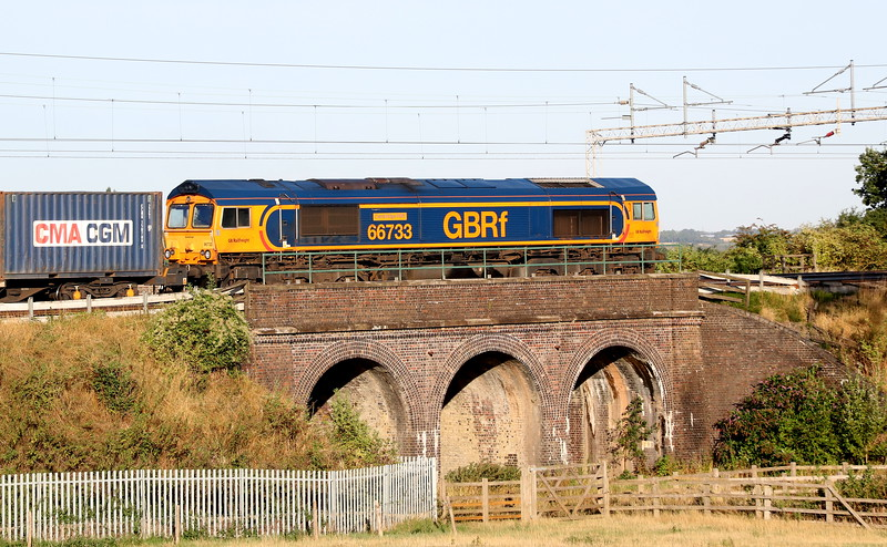 17 August 2018. 66733 Cambridge PSB passes North at Three Arches, Castlethorpe with the 4M21 0310 Felixstowe - Trafford Park.