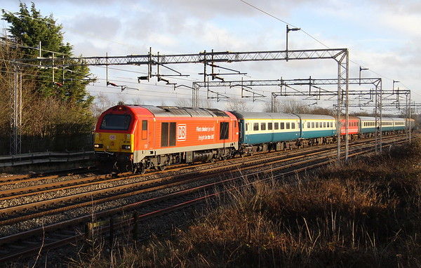 1 January 2018. New Years Day sun as 67010 passes Castlethorpe running as the 5Z75 1111 King's Cross - Burton Wetmore Sidings ECS. The skip and stock had been used along with 90018 (which was the main tour engine) on the Stoke Travel operated, Hogmanay Special from King's Cross to Edinburgh and return.