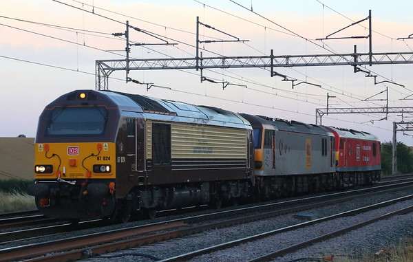 31 July 2018. The end of the day and the month as 67024 + 92036 Bertolt Brecht + 92015 pass Hanslope Junction working 0K06 1946 Wembley - Crewe Electric Depot.