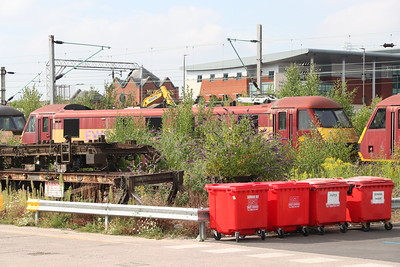21 July 2018. The former Rail express systems, 90017 stands forlornly behind a bush at Crewe Electric Depot. She had been removed from traffic in November 2006 with an electrical fault.