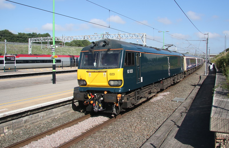 30 June 2018. 92023 takes the platform 1 route through MK with the delayed 1M16 2045 Inverness - Euston sleeper which was running 109 minutes late as it passed the camera due to the Fort William portion being heavily delayed into Edinburgh due to a lineside fire at Bathgate.