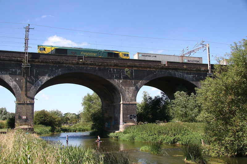 30 June 2018. 66418 PATRIOT - IN MEMORY OF FALLEN RAILWAY EMPLOYEES passes over Haversham Viaduct with the 4L90 0830 Lawley Street - Felixstowe. Note the  young lady and her male companion attempting to use a surfboard with empty Coke bottles attached for buoyancy !!!!
