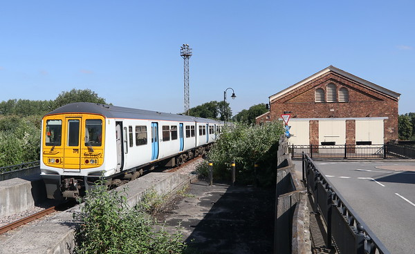 30 June 2018. 319372 is shunted out of Wolverton Works and along McConnell Drive by 08629 Wolverton (just visible). Note the former Royal Train shed on the right, now used for residential housing.