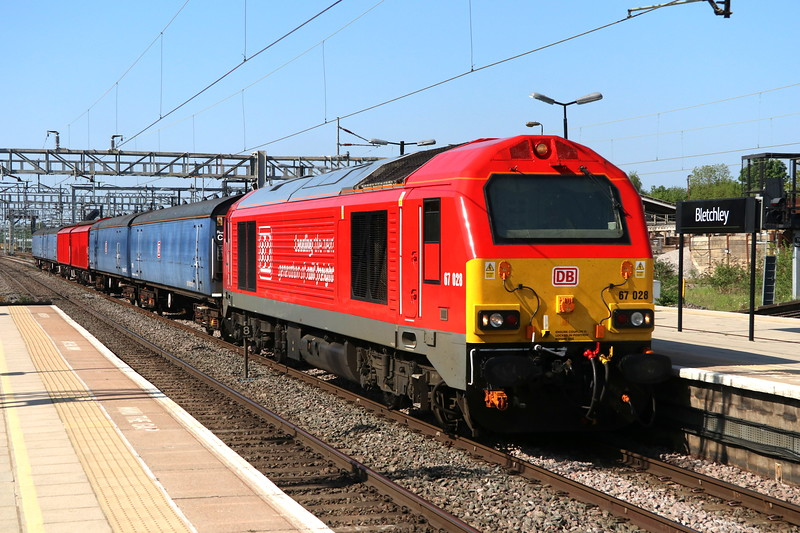 7 May 2018. Sparkling in DB red, 67028 passes Bletchley with the 6Z27 1330 Bescot Down Side - Wembley with four Porterbrook blue barrier vehicles, 6376/6377/6378/6379 interspersed by two red RBA vehicles, namely 210614 + 210493.