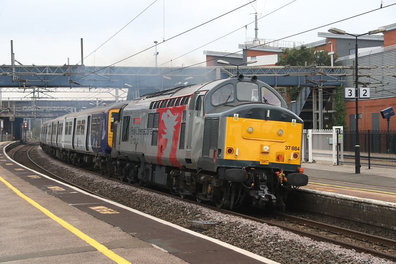 5 October 2018. 37884 Cepheus has 319450 for company passing through Wolverton on the start of their journey with the 5Q99 1630 Wolverton Centre Sidings - Loughborough Brush.