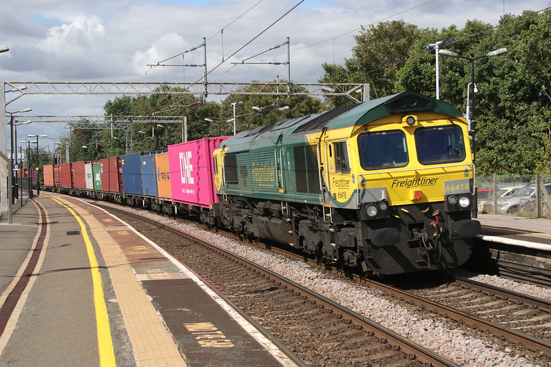 7 September 2018. The eye is drawn to the striking pink ONE (Ocean Network Express) box directly behind Powerhaul 66418 PATRIOT - IN MEMORY OF FALLEN RAILWAY EMPLOYEES passing Wolverton with the 4L46 1212 Lawley Street - London Gateway.