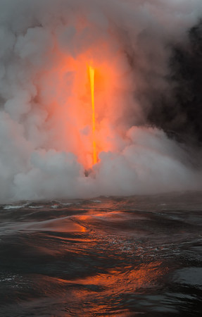 It was difficult to photograph from the moving boat; the explosions and steam often obscured sight of the lava flow. Here, the steam opened up to reveal almost the whole 45 foot cascade of lava, along with the surrounding glow and the reflection in the ocean.