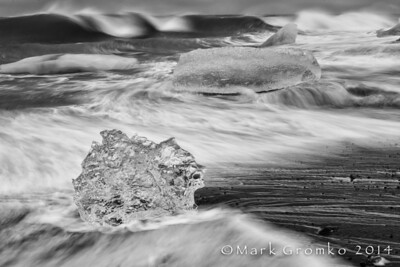 A glacier calves icebergs into a lagoon (Jokulsarlon). At low tide, the icebergs are carried by a strong rip out to the ocean, where they are beaten back on to the black sand beach by the wind and waves. 2nd, B&W prints, N4C, April 2014