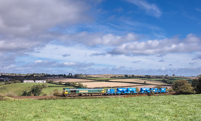 051017  66957  passes Menheniot with the 6Z77 08:55 Exeter Riverside to Exeter Riverside via Fairwater / Par.The terraced cottages of Pool hall farm stand out in the autumnal sunshine