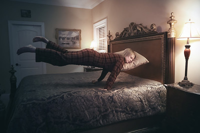 Floating woman sleeping above bed