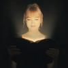 Woman reading a glowing Bible.