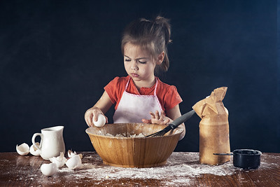 A little girl baking in the kitchen